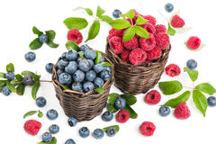 Blueberry and raspberry with leaves in a baskets Royalty Free Stock Photos
