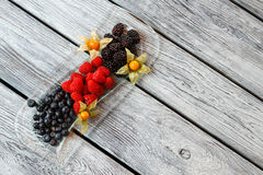 Blueberry and raspberry on plate. Berry dessert on wooden background. Fresh sweet berries. Add vitamins to your diet Stock Images