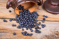 Blueberry or raspberry scattered from pot over wooden background. Health and diet concept. Copy space Stock Photo