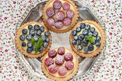 Blueberry and raspberry tartlets. On a silver platter Royalty Free Stock Image