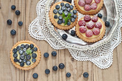 Blueberry and raspberry tartlets. On a silver platter Royalty Free Stock Photos
