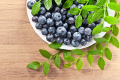 Blueberry. Ripe berries and green leaves on  wooden table Stock Photo