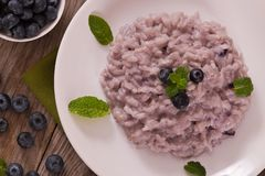 Blueberry risotto with mascarpone. Blueberry risotto with mascarpone on white dish stock image