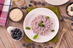 Blueberry risotto with mascarpone. Blueberry risotto with mascarpone on white dish royalty free stock photo