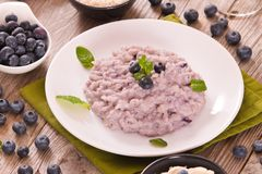Blueberry risotto with mascarpone. Blueberry risotto with mascarpone on white dish royalty free stock image