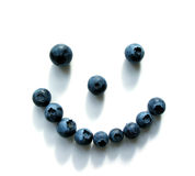 Blueberry smiley face. Smiley face made out of blueberries on white background...shadows add teeth stock photo