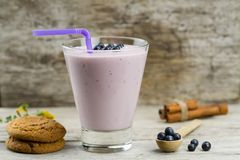 Blueberry smoothie with berries, cinnamon, oat cookies on wooden background. Healthy vegetarian food Stock Photos