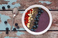Blueberry smoothie bowl with on a rustic old wood background Royalty Free Stock Image