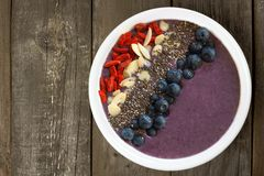 Blueberry smoothie bowl with super-foods on rustic wood Royalty Free Stock Photos