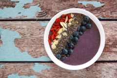 Blueberry smoothie bowl with superfoods on rustic old wood Stock Photos