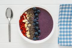 Blueberry smoothie bowl on white wood with cloth and spoon Royalty Free Stock Images