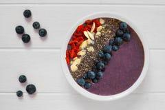 Blueberry smoothie bowl on white wood Royalty Free Stock Image