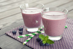 Blueberry smoothie. With fresh berry and drink straws on wooden background Stock Image