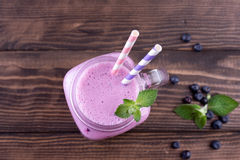 Blueberry smoothie in a glass jar with a straw and mint, and some fresh berries. Old vintage wooden background Royalty Free Stock Photography