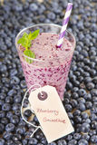 Blueberry smoothie in a glass jar with a straw and sprig of mint Stock Photography