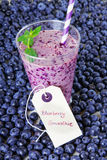 Blueberry smoothie in a glass jar with a straw and sprig of mint Royalty Free Stock Photo