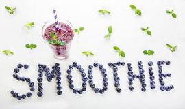 Blueberry smoothie in a glass jar with a straw and sprig of mint Stock Photos