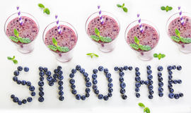 Blueberry smoothie in a glass jar with a straw and sprig of mint Royalty Free Stock Photography