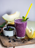 Blueberry smoothie in a glass with a straw and sprig of mint, ov Royalty Free Stock Images