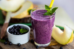 Blueberry smoothie in a glass with a straw and sprig of mint, ov Stock Photo
