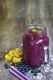 Blueberry smoothie in a mason jar . Blueberry smoothie in a mason jar on a wooden table.Rustic style stock photo