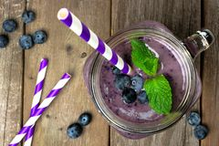 Blueberry smoothie with mint in mason jar above view. Blueberry smoothie with mint in mason jar mug with straw. Overhead view on wood Stock Photography