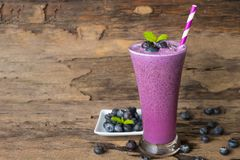 Blueberry smoothie purple colorful fruit juice milkshake blend beverage healthy high protein the taste yummy In glass,drink episod. E morning on a wooden stock photography