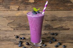Blueberry smoothie purple colorful fruit juice milkshake blend beverage healthy high protein the taste yummy In glass,drink episod. E morning on a wooden royalty free stock photography