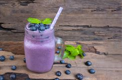 Blueberry smoothie purple colorful fruit juice milkshake blend beverage healthy high protein the taste yummy In glass,drink episod. E morning on a wooden stock image
