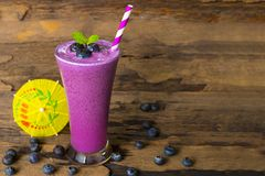 Blueberry smoothie purple colorful fruit juice milkshake blend beverage healthy high protein the taste yummy In glass,drink episod. E morning on a wooden royalty free stock image