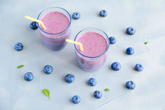 Blueberry Smoothie. Purple Smoothie in Glasses and some Fresh Berries around. Blueberry, banana, milk and honey are ingredients of a cocktail. Healthy concept Royalty Free Stock Photo