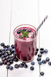 Blueberry smoothie on a wooden white background. Glass of smoothie with berry and mint. Fruit Healthy food. Breakfast. Blueberry smoothie on a wooden white stock photo