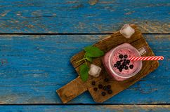 Blueberry smoothies on blue wooden boards from top view