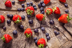 Blueberry and strawberries on wood in nature Royalty Free Stock Photography