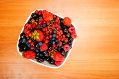 Blueberry, strawberry, raspberry, black and red currant in  bowl. On table Stock Photos