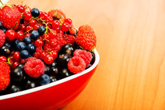 Blueberry, strawberry, raspberry, black and red currant in red. Bowl on table Royalty Free Stock Image
