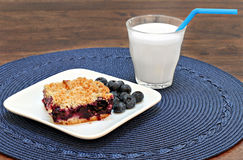 Blueberry streusel cookie bars with a glass of milk. Stock Photography