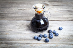 Blueberry syrup in glass bottle or mixture,. On wooden background Royalty Free Stock Photos