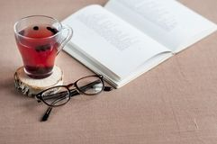 Blueberry tea in a clear glass cup on a round wooden stand with glasses. And a open book on a brown tablecloth Stock Image