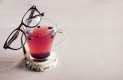 Blueberry tea in a glass cup and with glasses in a brown frame on it,. Space for text. anthocyanin to strengthen vision stock image