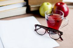 Blueberry tea to strengthen vision with empty white paper, eyeglasses. Against the background of books and apples Royalty Free Stock Photos