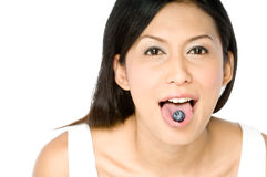 Blueberry on tongue. A young pretty Asian woman with a blueberry on her tongue Royalty Free Stock Photo