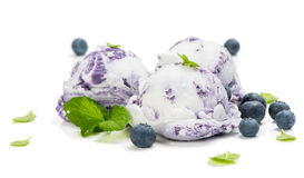 Blueberry and vanilla  ice cream. Vanilla and blueberry marble ice cream decorated with mint and fresh berries isolated on white background Stock Photos