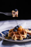 Blueberry waffle. Set in a nice dish and a fork cut in piece with black background copy space Royalty Free Stock Image