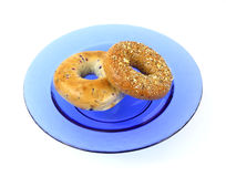 Blueberry and whole wheat grain bagels on blue dis Stock Photos
