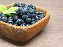 Fresh blueberry in a wooden bowl close-up on a wooden background. stock images