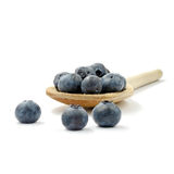 Blueberry Wooden Spoon. Studio macro of fresh blueberries on an old wooden spoon against a white background. Copy space stock image