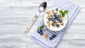 Blueberry yoghurt with muesli. Fresh blueberry yogurt with granola and mint on a background stock photos