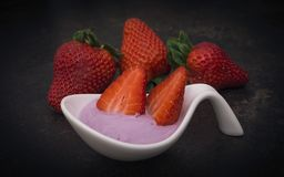 Blueberry yoghurt and strawberries. Blueberry yoghurt with some strawberries. Blurry background royalty free stock photo