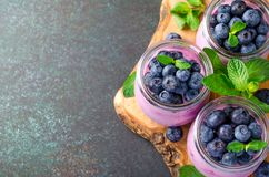 Blueberry yogurt with blueberries and mint. Three glasses of blueberry yogurt with blueberries on a wooden board and dark stone background. High angle view, copy Royalty Free Stock Photos